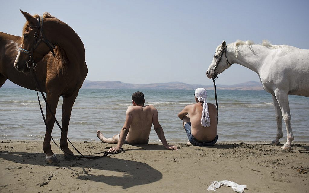 In this Saturday, September 23, 2017 photo, Israeli Druze men sit with their horses on the shores of the Sea of Galilee near the northern Israeli Kibbutz of Ein Gev. (AP Photo/Oded Balilty)
