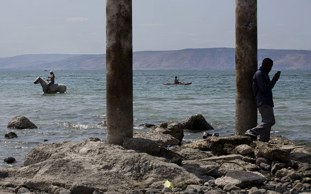 In this September 23, 2017 photo, people enjoy the Sea of Galilee near the northern Israeli Kibbutz of Ein Gev. (AP Photo/Oded Balilty)