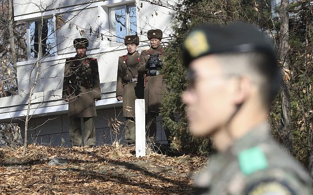 In this Nov. 27, 2017, file photo, North Korean soldiers look at the South side as a South Korean stands guard near the spot where a North Korean soldier crossed the border on Nov. 13 at the Panmunjom, in the Demilitarized Zone, South Korea. (AP Photo/Lee Jin-man, File)