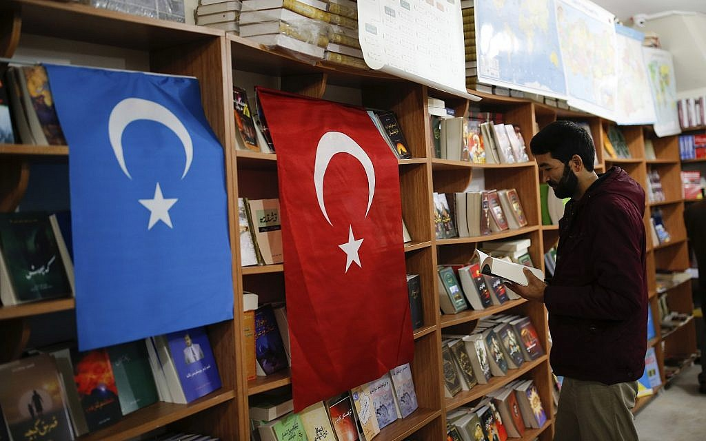 In this photo taken Thursday, Dec. 14, 2017, a man reads a book in a bookstore where flags which represents Turkey and 'East Turkistan,' the name Uighurs who oppose Chinese rule call their homeland, are hung in Istanbul's Zeytinburnu neighborhood. (AP Photo/Emrah Gurel)