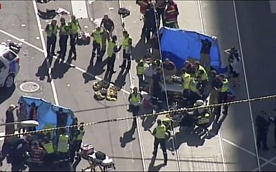 In this screenshot from a video from the Australian Broadcasting Corp., emergency medical workers offer aid to victims struck by a vehicle, December 21, 20217, in Melbourne, Australia. (Australian Broadcast Corp. via AP)