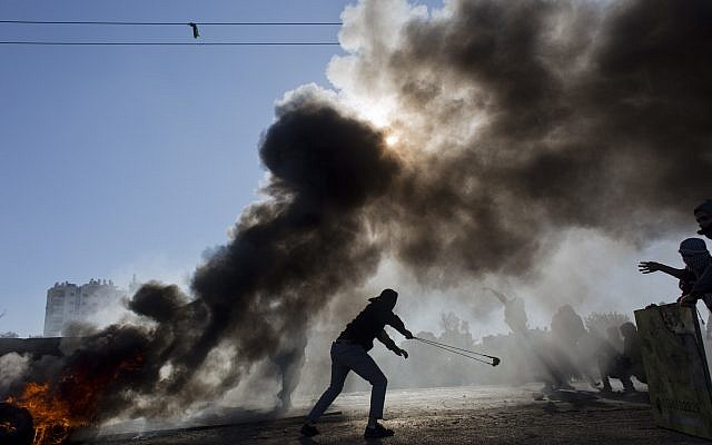 Illustrative. Palestinian protesters burn tires and clash with Israeli troops following protests against US President Donald Trump's decision to recognize Jerusalem as the capital of Israel, in the West Bank city of Ramallah, December 8, 2017. (AP Photo/Nasser Nasser)