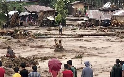 Villagers cross raging flood waters in Lanao del Norte, Zamboanga Pennisula, southern Philippines on Friday, December 22, 2017 (Aclimah Disumala via the AP)
