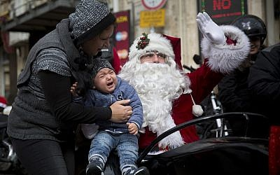 A man dressed as Santa Claus waves from a sidecar of a motorbike on Christmas Eve in Jerusalem Old City, Decemeber 24, 2017. (AP Photo/Oded Balilty)
