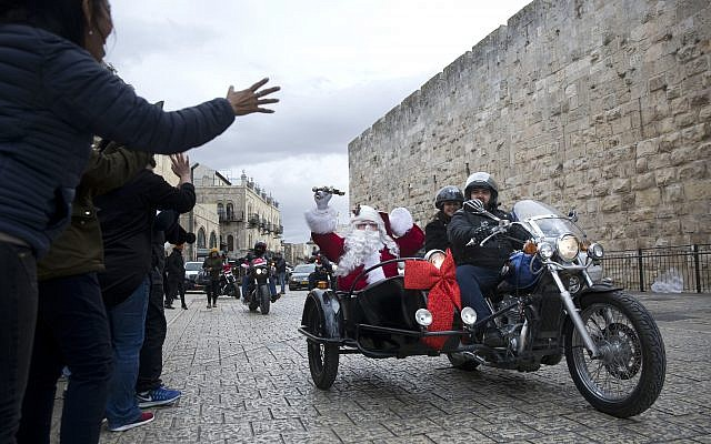 A man dressed as Santa Claus swaves from a sidecar of a motorbike on Christmas Eve in Jerusalem Old City Sunday, Dec. 24, 2017. (AP Photo/Oded Balilty)