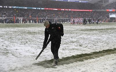 A worker clears snow from field lines at Soldier Field during an NFL football game between the Chicago Bears and Cleveland Browns in Chicago, December 24, 2017. (AP Photo/Charles Rex Arbogast)
