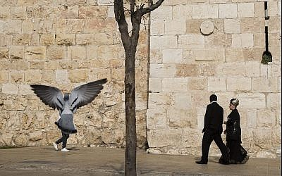 In this photo from December 23, 2017, people walk along the Old City of Jerusalem's walls, next to Jaffa Gate. (AP Photo/Oded Balilty)