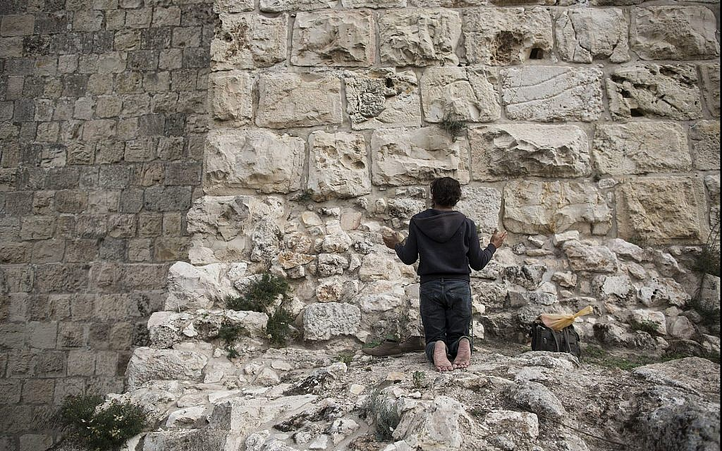 In this photo from December 19, 2017, a man prays facing Jerusalem's Old City walls between Jaffa Gate and Zion Gate. (AP Photo/Oded Balilty)