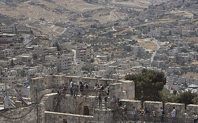 People tour the Jerusalem Ramparts Walk on Jerusalem's Old City walls overlooking the East Jerusalem neighborhood of Silwan,  May 24, 2017. (AP Photo/Oded Balilty)