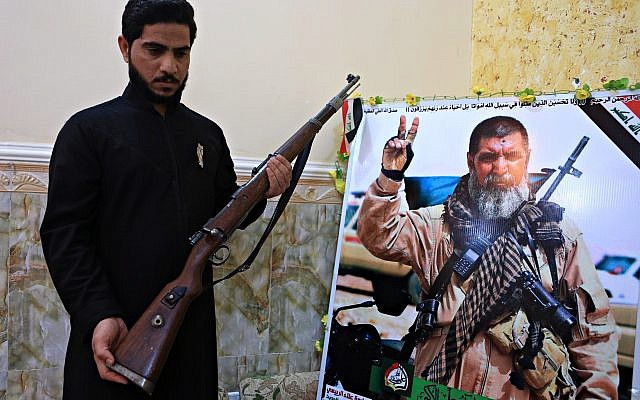 In this Tuesday, Dec. 5, 2017 photo, Talib, the son of Iraqi sniper Ali Jayad al-Salhi, 65, a volunteer with Popular Mobilization Forces killed fighting Islamic State militants, poses with a weapon next to his father's poster in his home in Basra, Iraq. (AP Photo/Nabil al-Jurani)