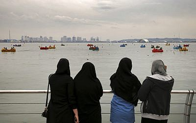 In this photo taken on April 2, 2017, women watch people riding boats on the Persian Gulf Martyrs lake, west of Tehran, Iran. (AP Photo/Ebrahim Noroozi)