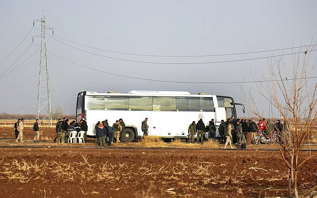 In this photo released on Friday, Dec. 29, 2017 by the Syrian official news agency SANA, Syrian government forces stand next to a bus which is waiting to evacuate Syrian rebels and their families from Beit Jinn village, in the southern province of Daraa, Syria. (SANA via AP)