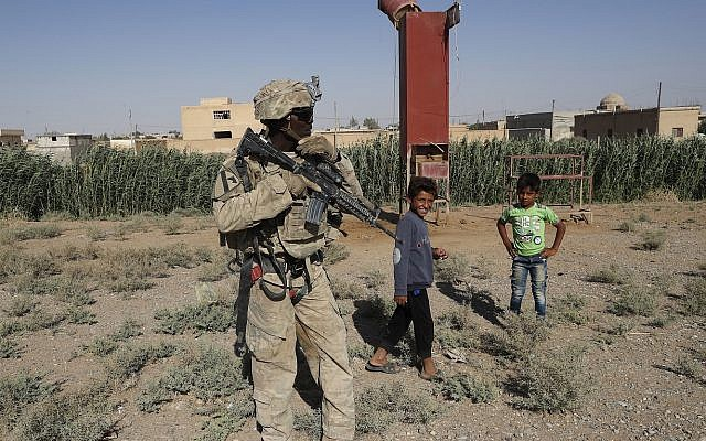 A US soldier stands near Syrian children on a road that links to Raqqa, Syria, Wednesday, July 26, 2017 (AP Photo/Hussein Malla)