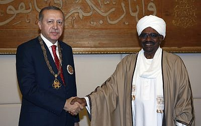 Sudan's President Omar al-Bashir, right, and Turkey's President Recep Tayyip Erdogan shake hands after al-Bashir presented Turkish leader with his country's highest medal during a ceremony in Khartoum, Sudan, Sunday, Dec. 24, 2017.(Kayhan Ozer/Pool Photo via AP)