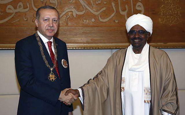 Sudan's President Omar al-Bashir, right, and Turkey's President Recep Tayyip Erdogan shake hands after al-Bashir presented Turkish leader with his country's highest medal during a ceremony in Khartoum, Sudan, Sunday, Dec. 24, 2017.(Kayhan Ozer/Pool Photo via AP)