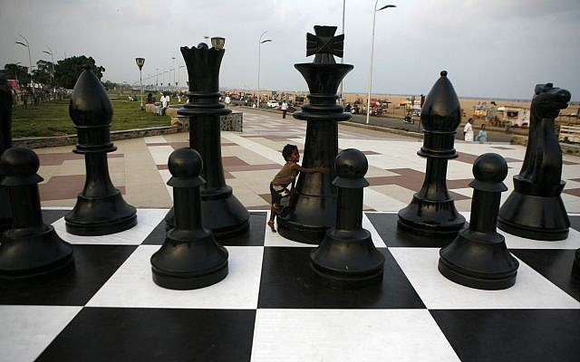 An Indian child plays around a huge chessboard model erected to mark the FIDE World Chess Championship at the Marina beach on the Bay of Bengal coast in Chennai, India, Thursday, November 7, 2013. (AP/Arun Sankar K )