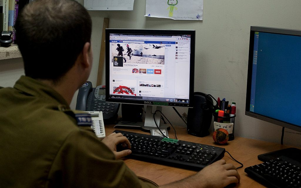Illustrative: A soldier looks at the IDF's Facebook page at the army spokesperson's office in Jerusalem in November 2012. (photo credit: AP/Sebastian Scheiner)