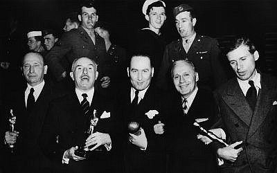 A quintet of 'Casablanca' winners: a sleepy Michael Curtiz, Jack Warner (talking, as usual), Hal Wallis (with his Thalberg Award), one of the event's hosts, Jack Benny, and the screenwriter Howard Koch. (Courtesy/author's collection)