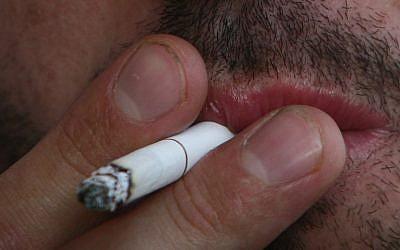 A man smokes a cigarette (Orel Cohen/ Flash90)