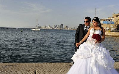 A couple has their picture taken before their wedding at the Jaffa Port, as the Tel Aviv skyline is seen in the background. (Serge Attal/Flash90)