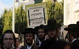 Ultra-Orthodox Jews stand in front of a sign in Beit Shemesh asking women not to loiter there on December 26, 2011. (Kobi Gideon/Flash90)
