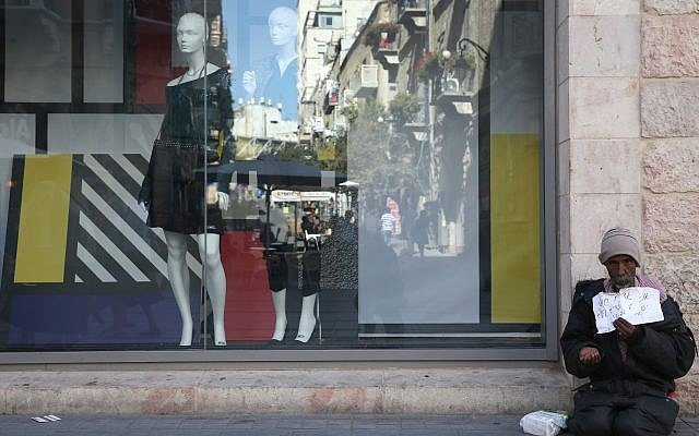 A man begs for money near a window display in the center of Jerusalem. October 22, 2013. (Nati Shohat/Flash90)