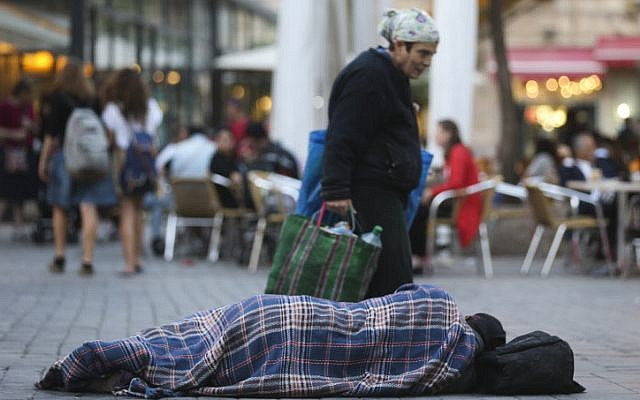 People walk by a homeless man sleeping on the street, near cafes in the center of Jerusalem. November 10, 2013. (Nati Shohat/FLASH90)
