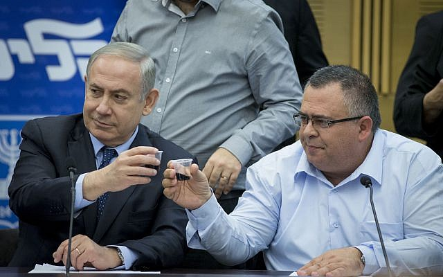 Prime Minister Benjamin Netanyahu, left, and David Bitan sharing a toast at a Likud faction meeting on February 27, 2017. (Yonatan Sindel/ Flash90)