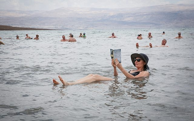 A woman reads a newspaper while floating in the Dead Sea, May 20, 2017. (Yossi Zamir/Flash90)
