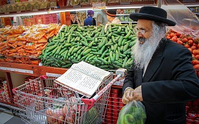 An ultra orthodox Jewish man studies Torah, as he shops for vegetables at a supermarket in Gush Etzion, on July 27, 2017. (Gershon Elinson/FLASH90)