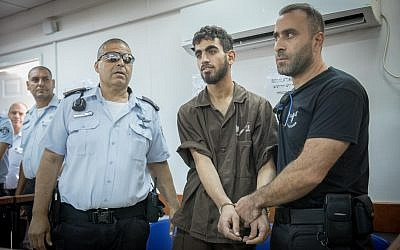 Omar al-Abed (center) is brought to the courtroom for his trial at the Ofer military court near the West Bank city of Ramallah on August 17, 2017. (Yonatan Sindel/Flash90)