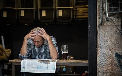 A man reads the newspaper at a cafe at the Mahane Yehuda Market in Jerusalem, on September 5, 2017. (Hadas Parush/Flash90)