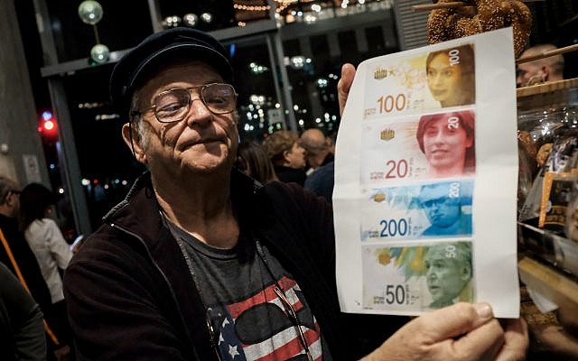 A protester holds an image of the portraits of Likud lawmakers on Israel's currency during the anti-corruption 'march of shame' in Tel Aviv on December 2, 2017. (Tomer Neuberg/Flash90)