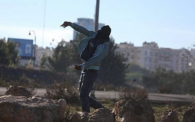 A Palestinian protester throws a rock at Israeli security forces during a violent protest near a checkpoint in the West Bank city of Ramallah on December 9, 2017. (Flash 90)