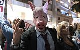 A protester wearing a pig mask attends a protest against government corruption in Tel Aviv on December 9, 2017.  (Tomer Neuberg/Flash90)