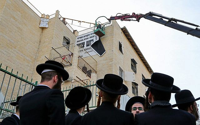 "Beit Shemesh municipal workers take down ""modesty"" signs in the city on December 11, 2017. (Yaakov Lederman/Flash90)"