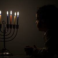 Illustrative:  A Jewish boy looks at a menorah on the Jewish holiday of Hanukkah in Jerusalem, on December 14, 2017. (Flash90)