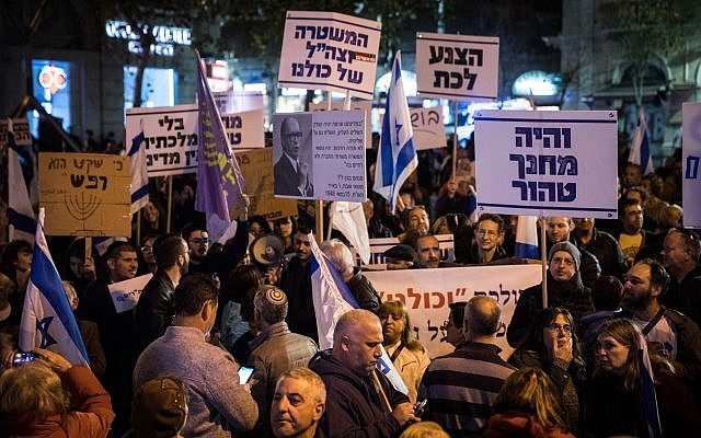 Israelis hold signs and shout slogans during a rally against corruption in government, at Zion Square in Jerusalem on December 23, 2017. (Hadas Parush/Flash90)