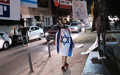 Israelis prepare for the weekly protest against the corruption of the government in Tel Aviv on December 30, 2017. (Tomer Neuberg/Flash90)