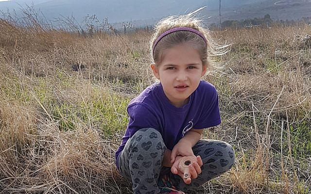 Seven-year-old Hadas Goldberg-Keidar from Kibbutz Heftziba with the intact 2,200-year-old clay lamp next to porcupines' cave in the Beit She'an Valley. (Israel Antiquities Authority)