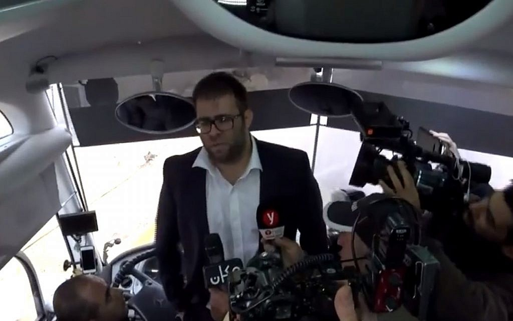 Likud MK Oren Hazan boards a bus carrying family members of Gazans being held in Israeli military prison, December 25, 2017. (Screen capture: Israel Hayom)
