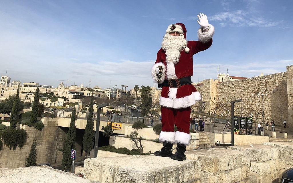 Jerusalem Santa, as portrayed by Issa Kassissieh, walking the ramparts of the Old City in Jerusalem, on December 21, 2017. (Jessica Steinberg/Times of Israel)