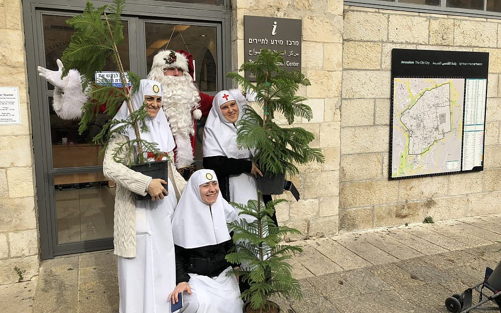 Jerusalem Santa, Issa Kassissieh, poses with locals coming to pick up free Christmas trees on Thursday, December 21 (Jessica Steinberg/Times of Israel)