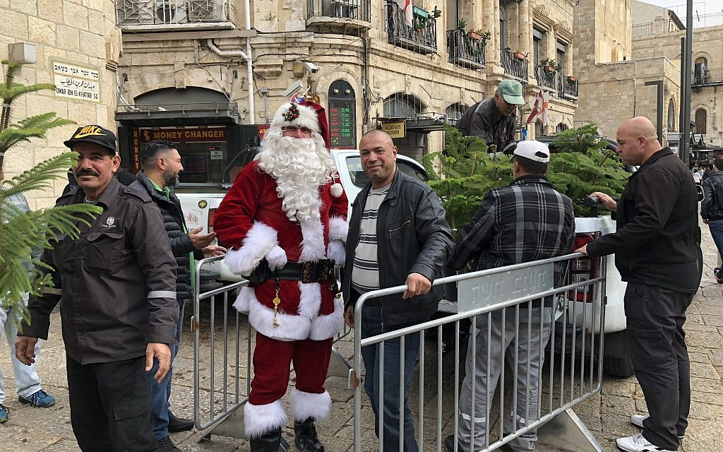 Jerusalem municipality workers unloading free Christmas trees handed out at Jaffa Gate on Thursday, December 21, 2017 (Jessica Steinberg/Times of Israel)