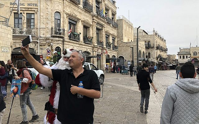 The Jerusalem Santa taking selfies outside Jaffa Gate on Thursday, December 21, 2017 (Jessica Steinberg/Times of Israel)