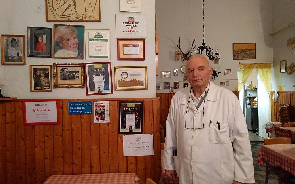 Sandor Orban, who has been running Kadar Etkezde for the last 30 years, next to his restaurant certificates and awards, and photos of celebrities who frequent the place. (Yaakov Schwartz/Times of Israel)