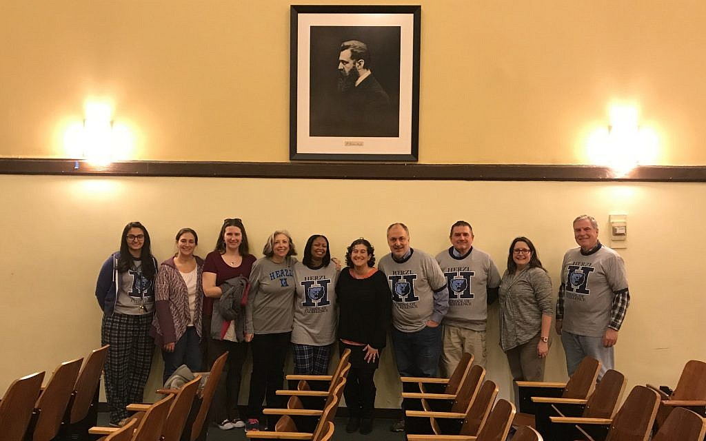 Temple Beth Israel's director of congregational learning Lori Sagarin (fourth from left), Theodore Herzl School principal Tamara Davis (fifth from left) and others beneath Theodor Herzl portrait donated to school by Herzl collector David Matlow, Chicago, December 18, 2017. (Courtesy)