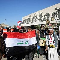 Iraqis wave the national flag at the Tahrir Square in the capital Baghdad on December 10, 2017, during a military parade to mark the end of a three-year war against the Islamic State group. (AFP PHOTO / AHMAD AL-RUBAYE)