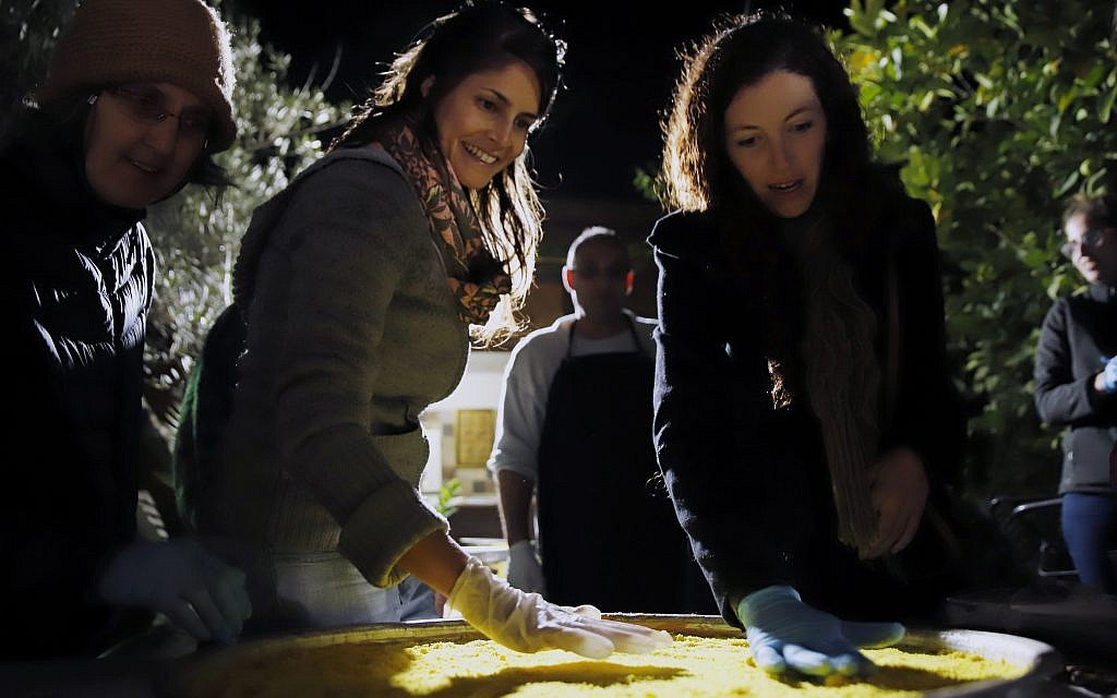 Making knafe, a traditional Palestinian dessert, on Sunday, December 3, 2017, in Beit Hanina, an Arab neighborhood of Jerusalem, as part of Open Holidays, a new event geared at understanding one anothers' traditions (Courtesy Open Holidays)