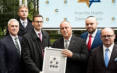 Mateusz Morawiecki, third from left, at the Warsaw Zoo holding a document honoring rescuers of Jews, Sept. 18, 2017. (Courtesy of From the Depths)